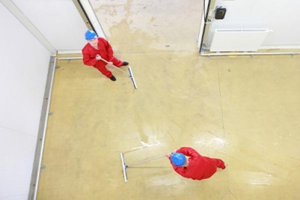 Panowie w czerwonych kombinezonach sprzątający sale